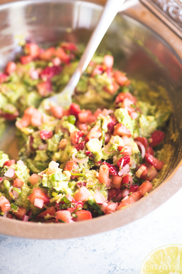 Switch up your guac game with this summery Strawberry Guacamole from http://meatified.com. Flecked with strawberries, green onion & mint for a fun twist on the classic favorite.