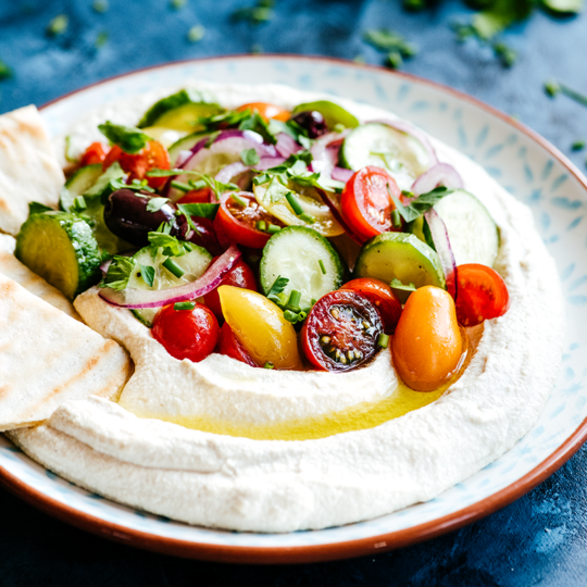 This silky smooth hummus leaves out the legumes but brings all the flavor, brightened with crunchy, fresh Mediterranean salad for the perfect summery meal.